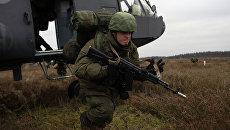 Десантник ВДВ высаживается из вертолета Ми-8 на летно-тактических учениях армейской авиации Западного военного округа