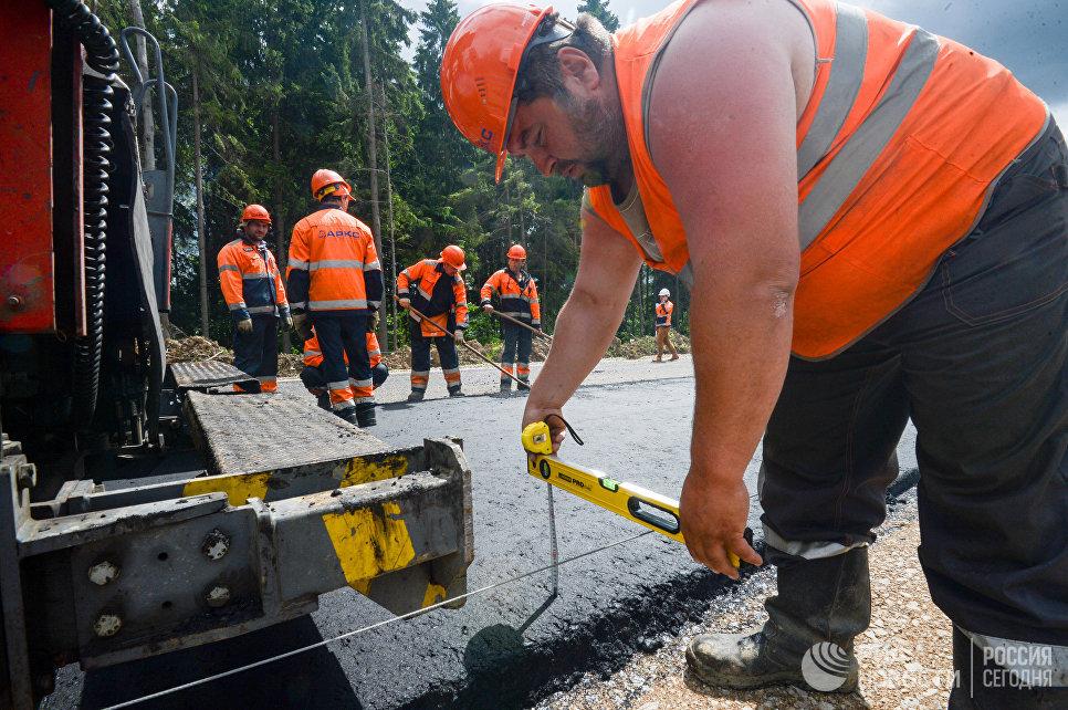 Рабочий во время дорожных работ на одном из участков пятого пускового комплекса ЦКАД в Московской области