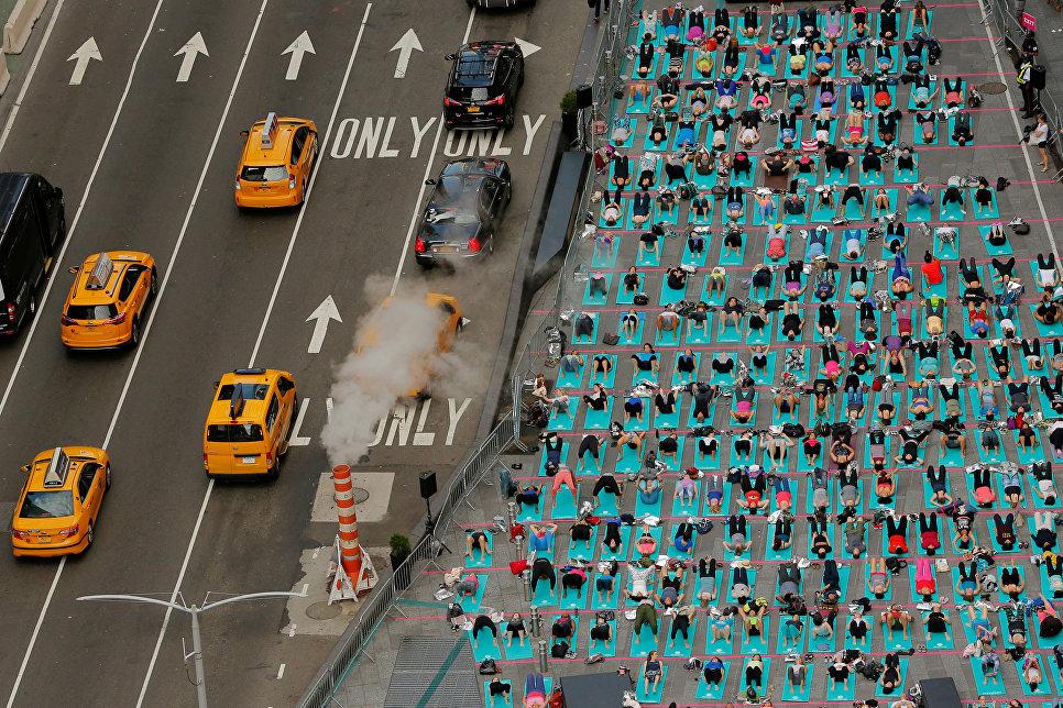 Люди занимаются йогой в день летнего солнцестояния в Нью-Йорке
