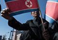 Мужчина с флагом КНДР в Пхеньяне
