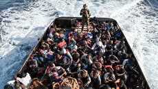 Сотрудник Ливийской береговой охраны во время спасения нелегальных мигрантов, пытающихся добраться до Европы, недалеко от Эз-Завия. Архивное фото