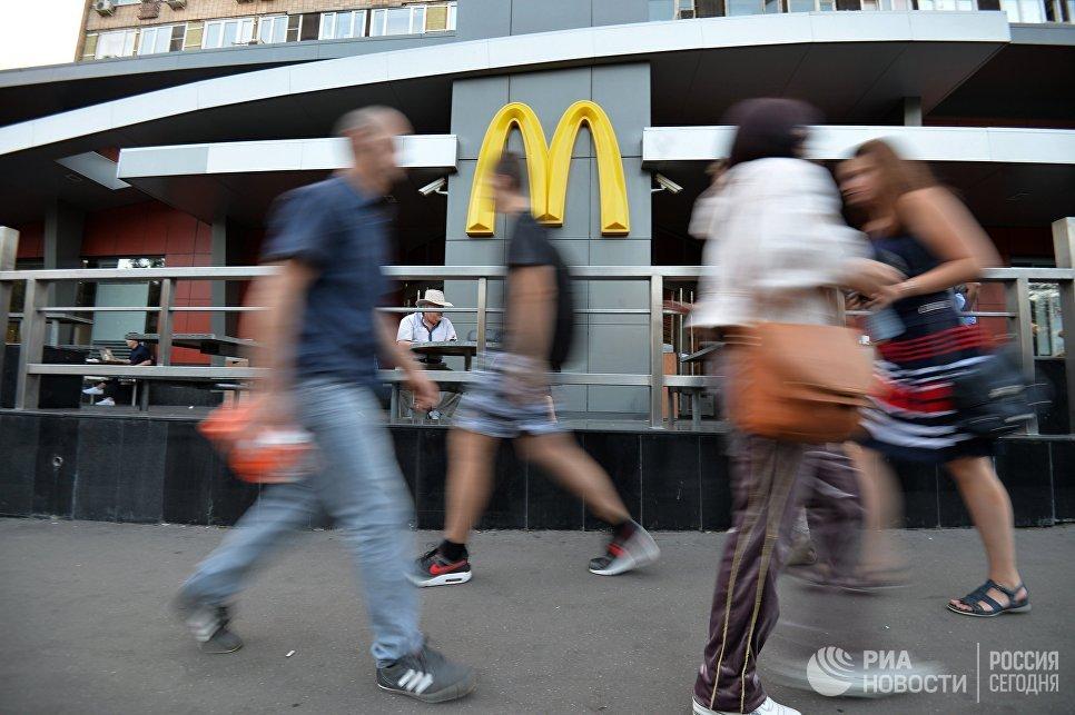 Люди проходят мимо ресторана быстрого питания Макдоналдс на улице Большая Бронная в Москве. Архивное фото