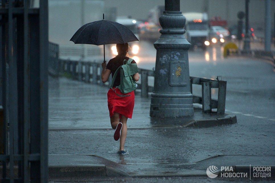 Девушка бежит с зонтом во время дождя в Москве