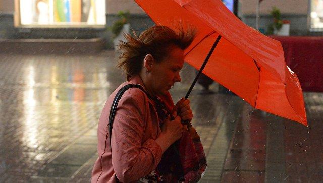 Женщина с зонтом во время дождя в Москве