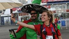 Болельщик сборной Мексики фотографируется с волонтером