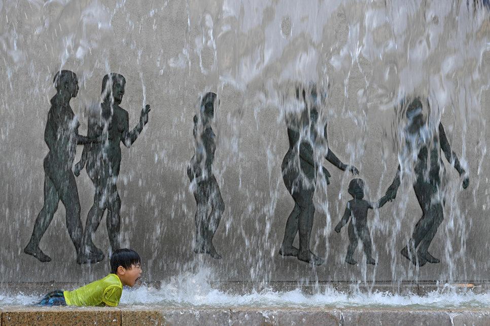 Ребенок купается в фонтане в Токио