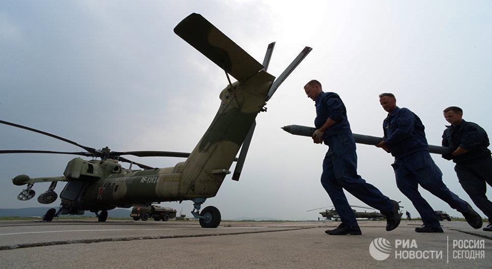 Авиационные техники готовят вертолет Ми-28 к вылету во время учений отдельного вертолетного полка на аэродроме Черниговка в Приморском крае