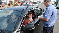 Сотрудник ГИБДД проверяет документы у автовладельца. Архивное фото