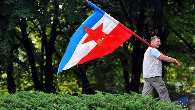 Мужчина с флагом Социалистической Федеративной Республики Югославия в Белграде
