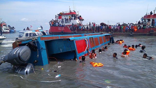 Поисково-спасательная команда помогает пассажирам опрокинутой лодки в Таракане. 25 июля 2017