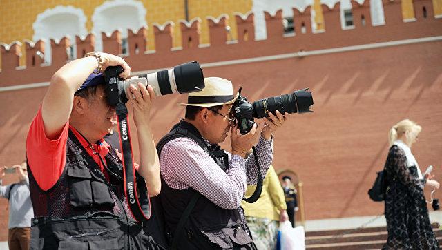 Туристы фотографируют в Александровском саду в Москве. Архивное фото