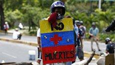 Мужчина с щитом Больше никаких смертей во время простестов в Каракасе, Венесуэла. 30 июля 2017