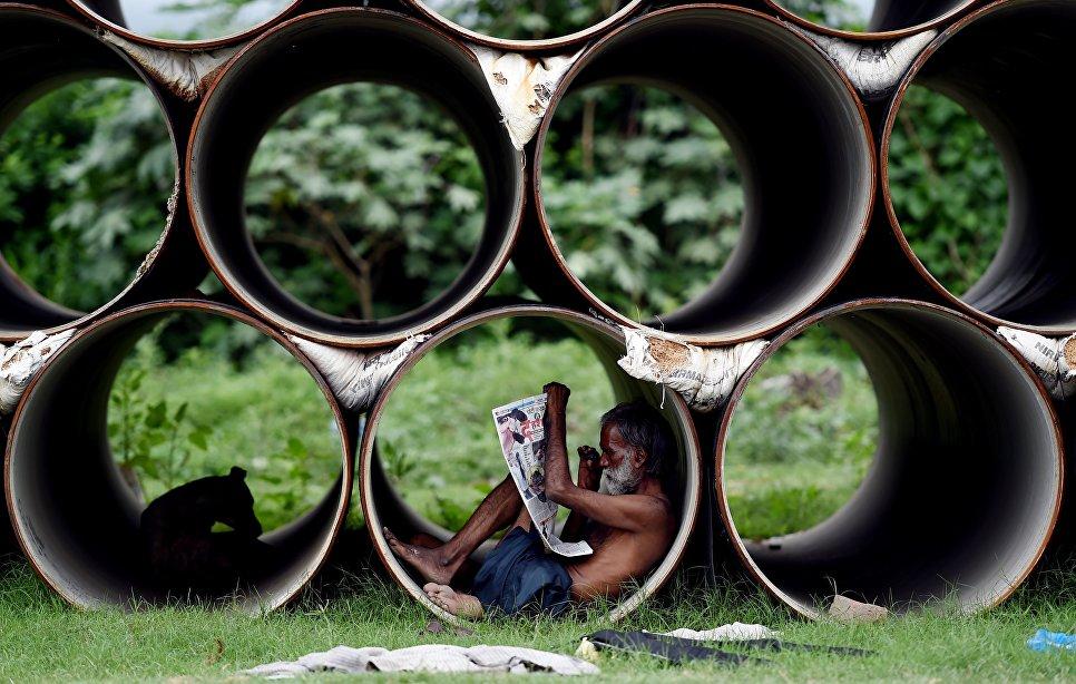 Мужчина читает газету, сидя в трубе. Нью-Дели, Индия