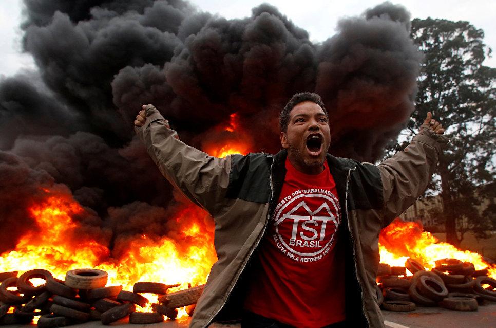 Член Бразильского движения бездомных рабочих во время протеста против президента Бразилии Мишеля Темера в Сан-Паулу