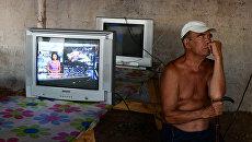 Мужчина смотрит телевизор на территории лагеря для беженцев с востока Украины. Архивное фото