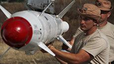 Российские военные подвешивают высокоточную ракету Х-25 к самолету Су-24 на авиабазе Хмеймим в Сирии
