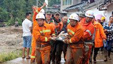Спасатели транспортируют пострадавшего при сходе селя в провинции Сычуань в Китае. 8 августа 2017