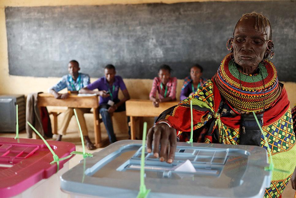 Женщина племени туркана бросает свой бюллетень на избирательном участке во время выборов в деревне Кении. 8 августа 2017