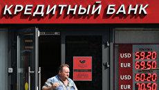 Мужчина выходит из отделения Московского кредитного банка.  Архивное фото