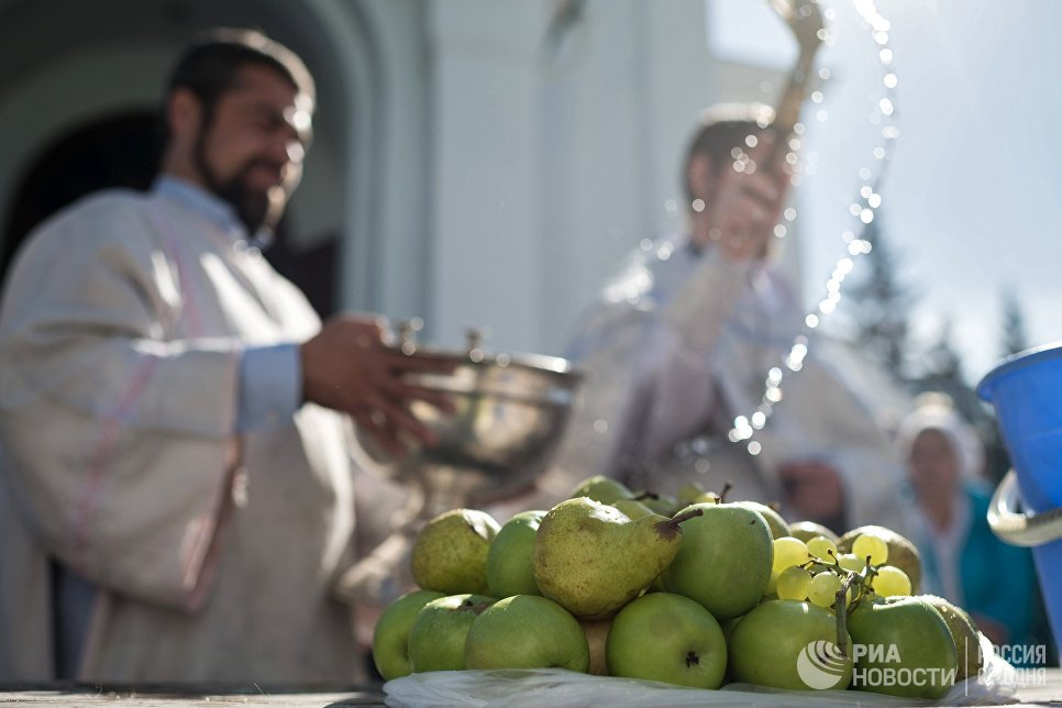 Священнослужитель окропляет святой водой яблоки и фрукты во время богослужения в честь праздника Преображения Господня у собора Воздвижения Креста Господня в Омске. 19 августа 2017
