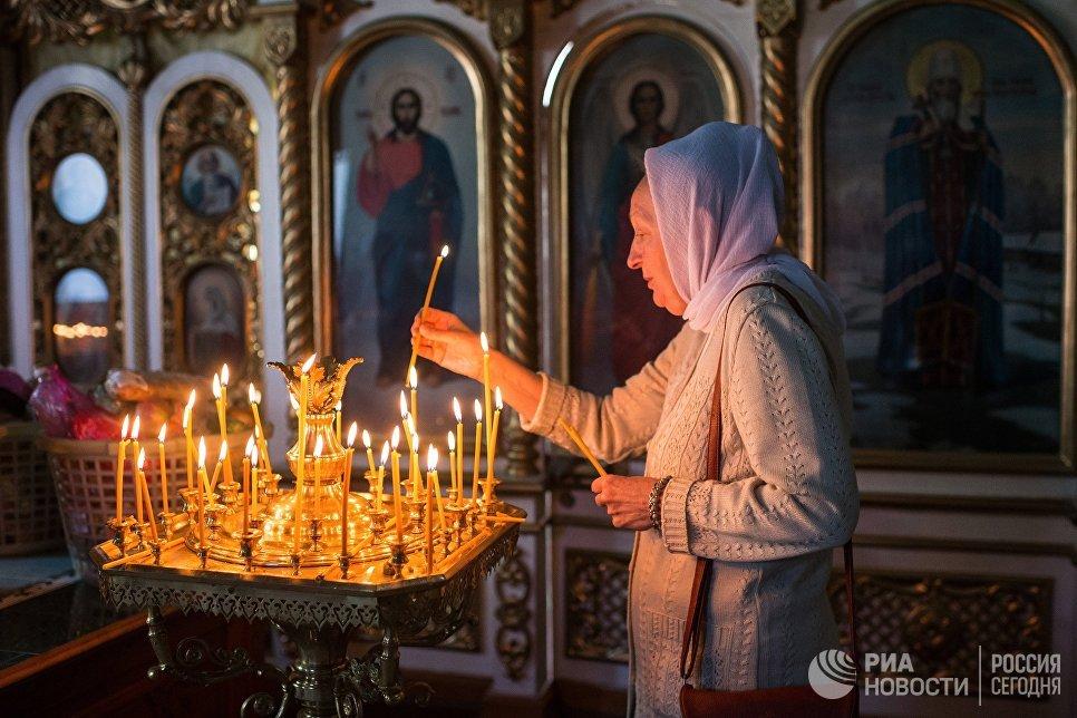 Женщина во время богослужения в честь праздника Преображения Господня в соборе Воздвижения Креста Господня в Омске. 19 августа 2017