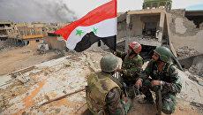 Сирийские военнослужащие с флагом