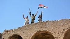 Мужчины с автоматом и Иракским флагом в городе Талль-Афар. Архивное фото