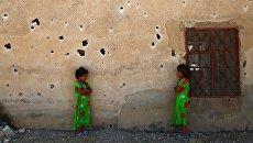 Сирийские девочки позируют фотографу на фоне изрешеченной пулями стены в деревне Кафр Гхан к северу от Алеппо