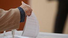 Избиратель кидает бюллетень в урну в единый день голосования на избирательном участке в Москве. Архивное фото