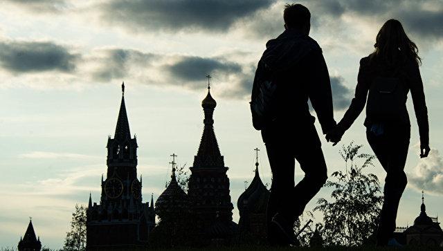 Москвичи на фоне Спасской башни Московского Кремля