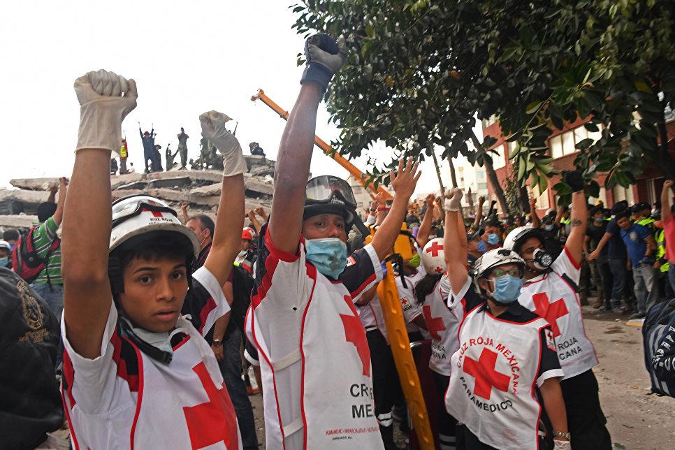 Спасатели просят тишины, чтобы услышать голоса возможных выживших под обломками здания, после землетрясения в Мехико. 19 сентября 2017