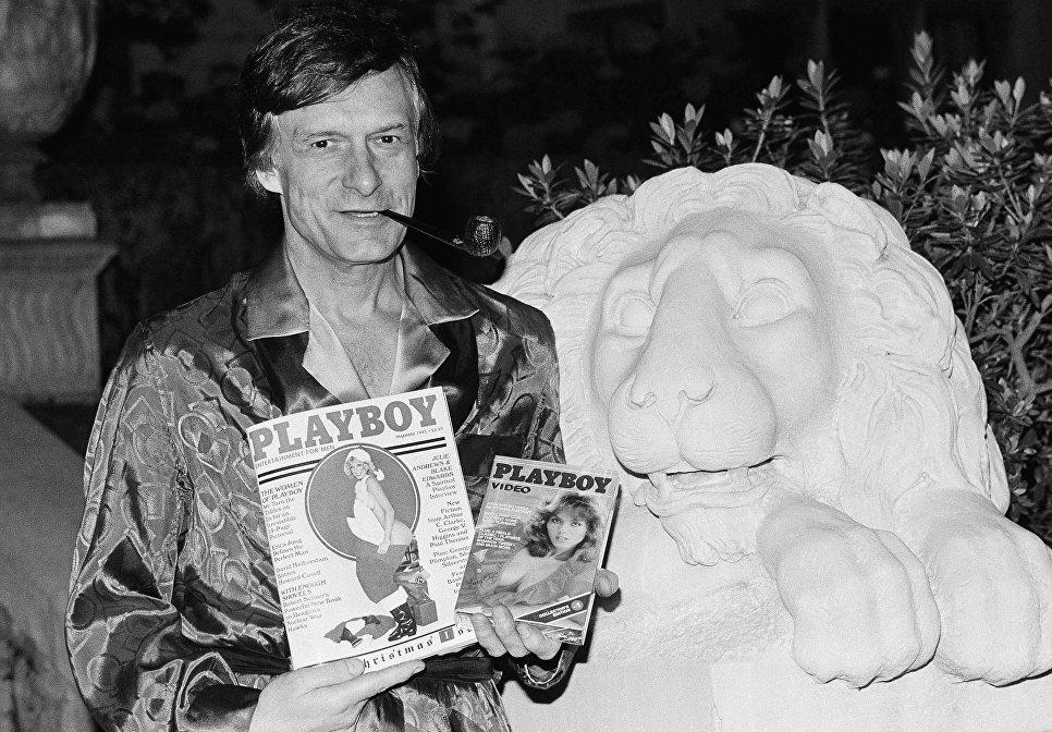 Хью Хефнер держит журнал Playboy и видеокассету с канала Playboy Channel во время интервью в особняке Playboy в Холмби-Хиллз. 29 ноября 1982
