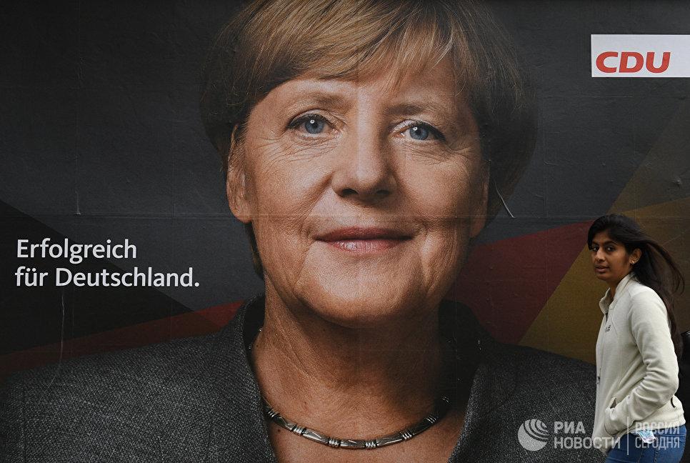 Плакат с изображением канцлера Ангелы Меркель на одной из улиц Берлина накануне парламентских выборов.