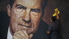Рабочий протирает портрет экс-президента США Ричарда Никсона в здании музея и библиотеки, названных в его честь, в Калифорнии