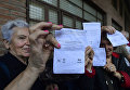 Женщины держат бюллетени на избирательном участке в Барселоне, Испания. 1 октября 2017