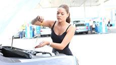 Девушка замеряет уровень масла в двигателе автомобиля