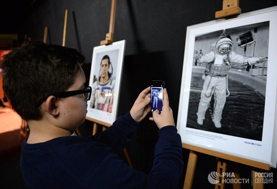 Посетитель фотографирует на фотовыставке МИА Россия сегодня в рамках премьеры фильма Салют-7 в кинотеатре Октябрь