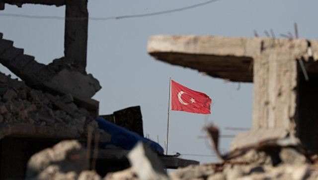 Турецкий флаг развивается на границе Турции и Сирии среди зданий, разрушенных в результате борьбы с ИГ*. 11 октября 2017