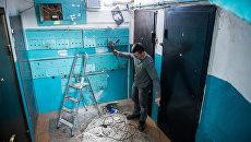 Рабочие регионального фонда капитального ремонта многоквартирных домов меняют электропроводку в подъезде жилого дома