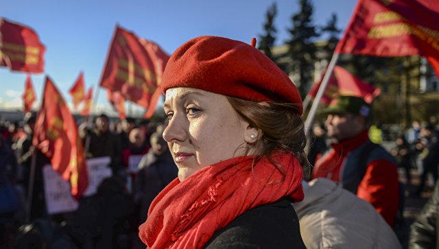 Участница митинга в честь 100-летия Великой Октябрьской социалистической революции у Финляндского вокзала в Санкт-Петербурге. 7 ноября 2017