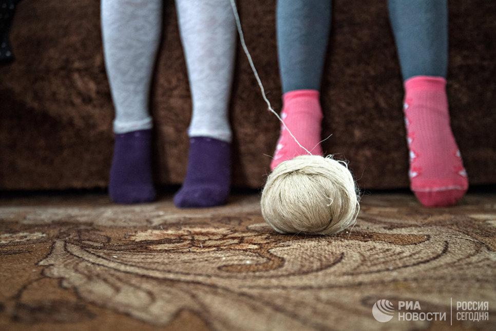 Дети послушно сидят у бабушки и учатся вязать.