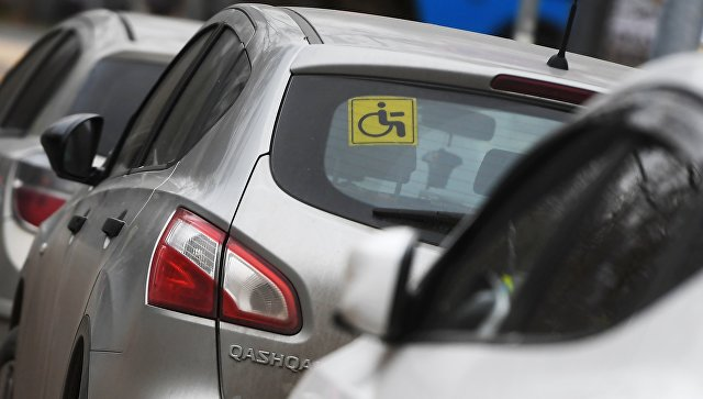 Опознавательный знак Инвалид под стеклом автомобиля в Москве