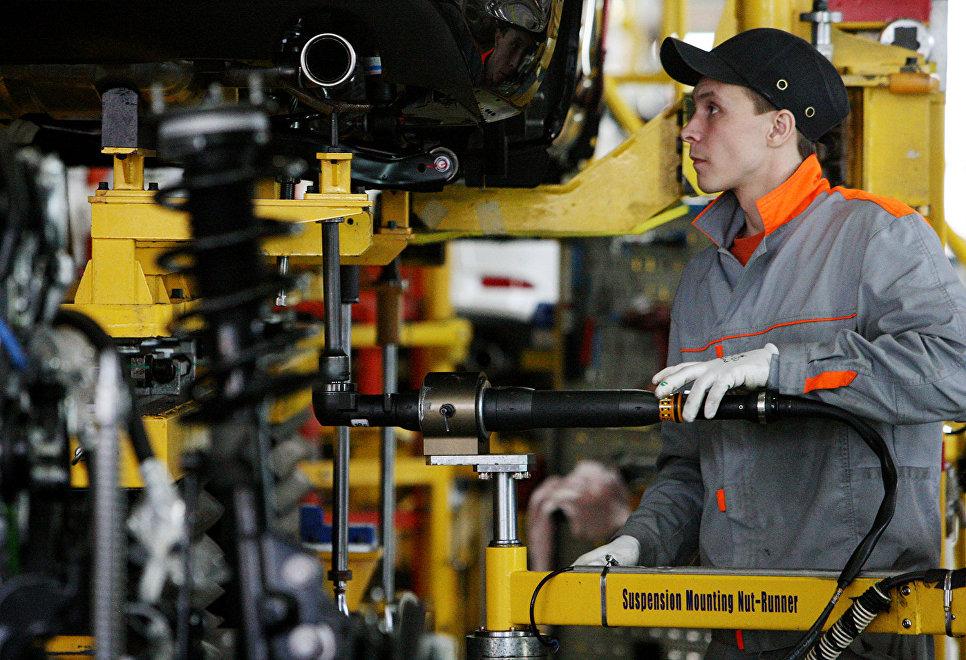 Сотрудник завода работает на линии сборки автомобилей. Архивное фото