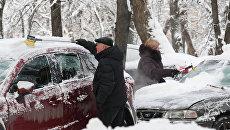 Горожане очищают личные автомобили от снега. Архивное фото