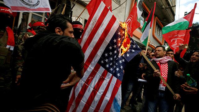 Палестинцы сжигают флаг США во время протеста против решения Трампа признать Иерусалим столицей Израиля в городе Газа. 7 декабря 2017