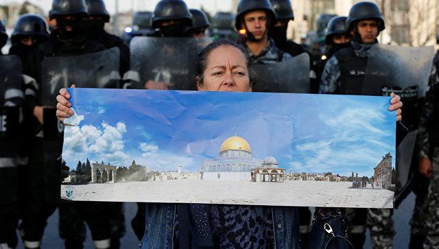 Протестующая держит плакат с изображением мечети Эль-Акса во время протеста возле американского посольства в Аммане, Иордания. 7 декабря 2017