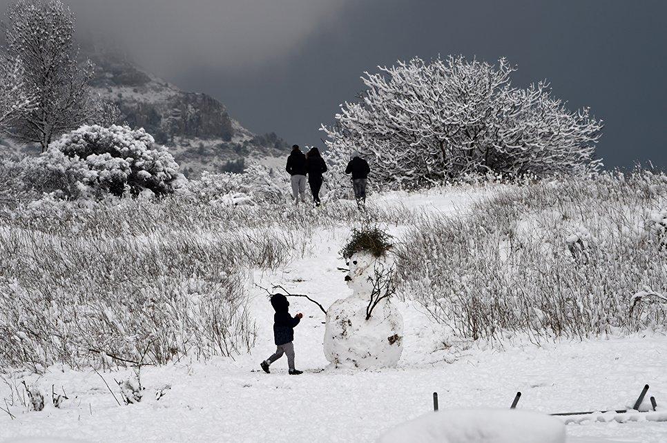 Ребенок играет рядом со снеговиком в окрестностях Марселя
