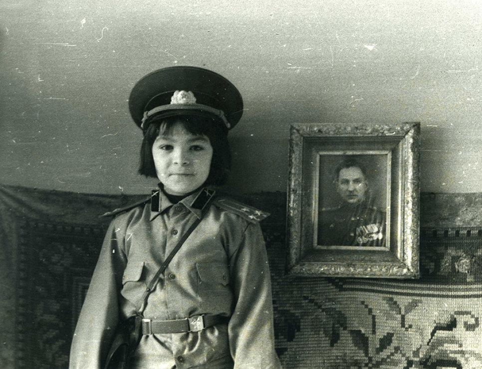 Автор книги позирует на фоне фотографии своего деда, полковника Льва Пунина. Ленинград, 1987 г.