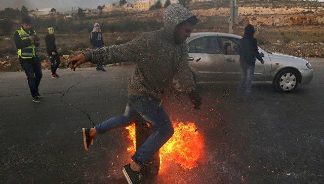 Протестующие во время столкновений на границе Палестины и Израиля в районе Рамаллы. 10 декабря 2017