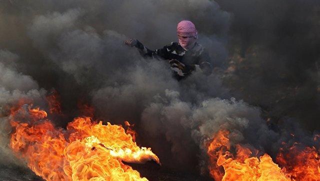 Протестующий во время столкновений на границе Палестины и Израиля в районе Рамаллы. 11 декабря 2017